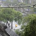写真: 上海 台風で暴風雨 雨合羽で自転車