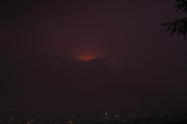 黒雲の上からわずかに覗いた花火。