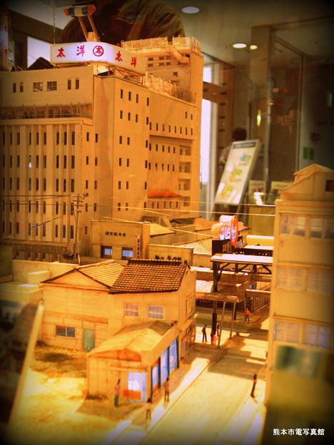 脇道から眺めた下通(しもとおり)の様子。大洋デパートと櫻井総本店が見えています。手前の建物は現在も営業中の手芸用品専門店のマキノさんです。