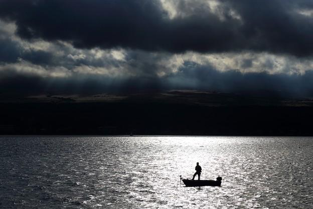 写真: 降り注ぐ光と釣り人