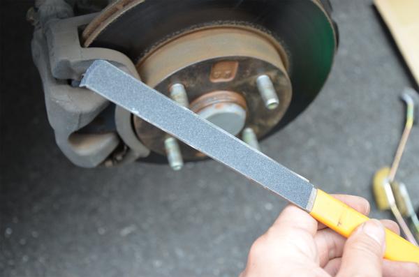 金属ヤスリに貼付けた耐水ペーパーで錆を削り落とす