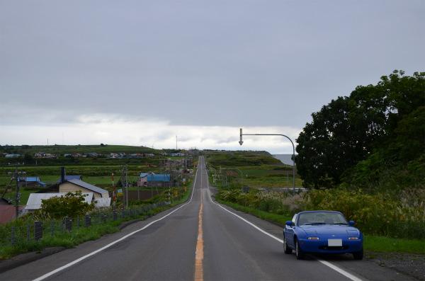 起伏のある長い直線道路とマリナーブルーのロードスター